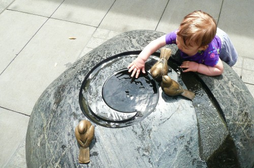 An adorable toddler plays in a water feature
