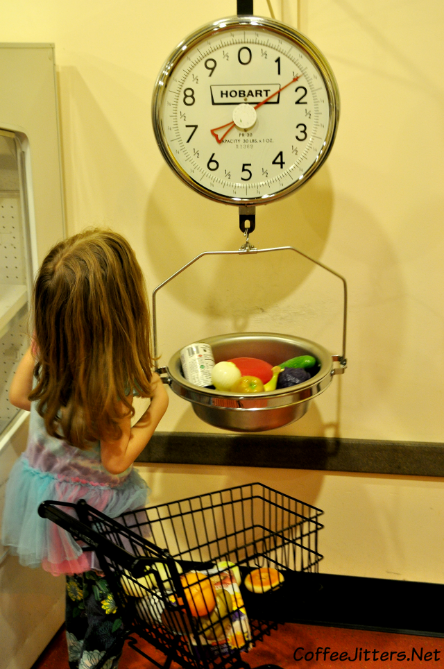 weighing her groceries on the scale at the seattle childrens museum